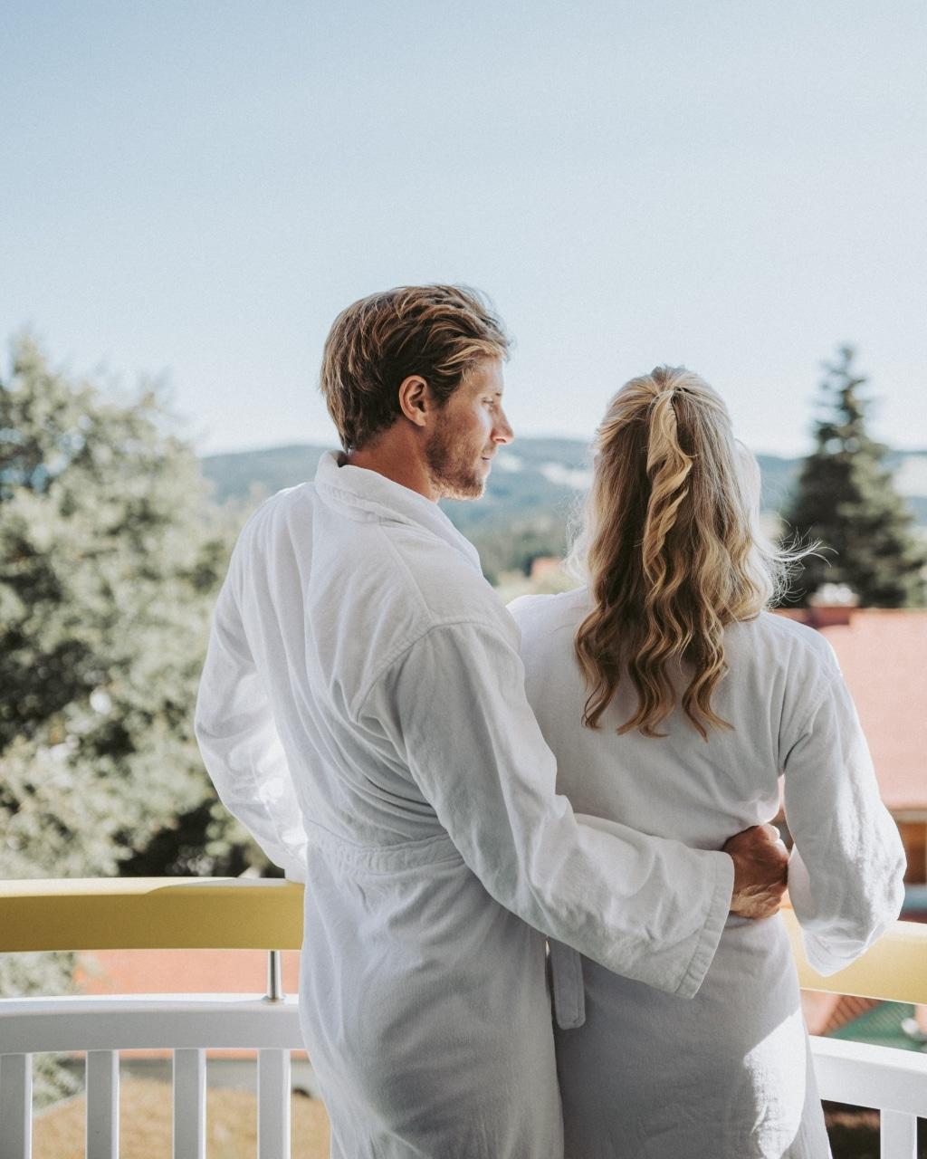 Paar in Bademantel auf Balkon
