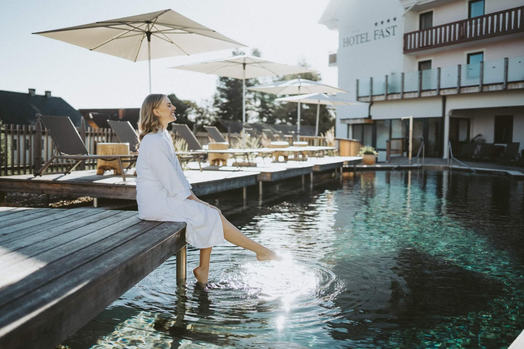 Frau sitzt am Rand von Pool, Beine im Wasser