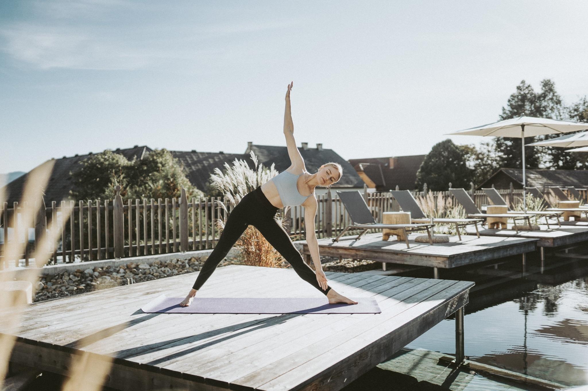 Frau macht Yoga am Poolrand